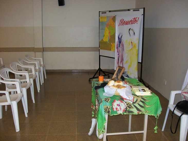 El salón preparado con la imagen, el mapa, y los símbolos: pan, calzado, cruz, cirio.